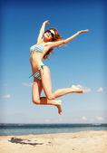 Kvinna i bikini hoppa på stranden — Stockfoto