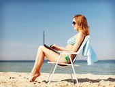 Dziewczynka, patrząc na komputer typu tablet na plaży — Zdjęcie stockowe