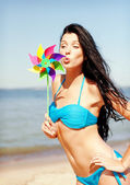 Girl with windmill toy on the beach — Stock Photo