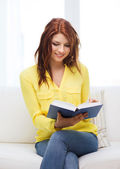 Smiling teenager reading book and sitting on couch — Stock Photo