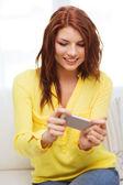 улыбающиеся женщина с смартфона на дому — Стоковое фото