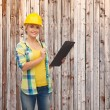 Smiling woman in helmet with clipboard — Stok fotoğraf