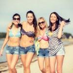 Girls in bikinis walking on the beach — Stock Photo #45169819