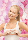 Smiling young woman showing heart shape gesture — Foto Stock