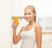 Smiling woman holding glass of orange juice — Stock Photo