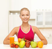 Smiling woman with organic food or fruits on table — Stock Photo