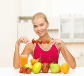 Smiling young woman with organic food on the table — Stock Photo
