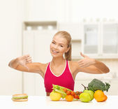 Woman with fruits and hamburger comparing food — Stock Photo