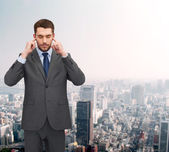 Annoyed businessman covering ears with his hands — Stock Photo