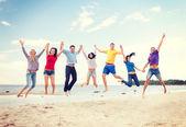 Grupo de amigos saltando na praia — Foto Stock