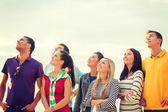 Group of friends looking up on the beach — Stock Photo