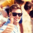 Man with friends on the beach showing thumbs up — Stock Photo #45170107