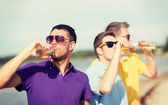 Friends on the beach with bottles of drink — Stock Photo