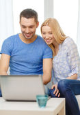 Smiling happy couple with laptop at home — Stock Photo