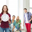 Young woman in casual clothes with wall clock — Foto Stock