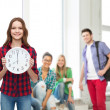 Young woman in casual clothes with wall clock — Stockfoto