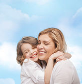 Happy mother and daughter hugging — Stock Photo