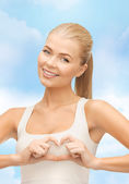 Smiling woman showing heart shape gesture — Stock Photo