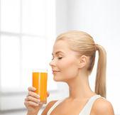 Молодая женщина питьевой апельсиновый сок — Стоковое фото