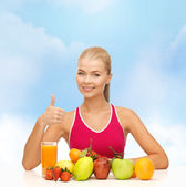 Smiling woman with organic food or fruits on table — Stock fotografie