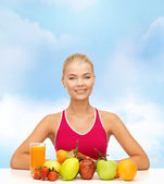 Smiling woman with organic food or fruits on table — Stockfoto