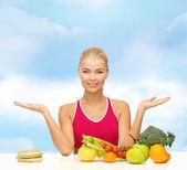 Smiling woman with fruits and hamburger — Stock Photo