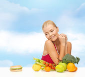 Doubting woman with fruits and hamburger — Stock Photo