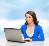 Smiling woman in blue clothes with laptop computer — Foto Stock