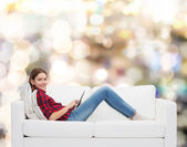 Teenage girl sitting on sofa with tablet pc — Stockfoto
