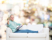 Smiling man lying on sofa with book — Stockfoto