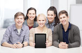 Smiling students with blank tablet pc screen — Stock fotografie