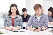 Estudiantes investigando smartphone en la escuela — Foto de Stock