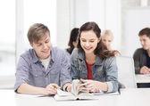 Dos adolescentes con cuadernos y el libro en la escuela — Foto de Stock
