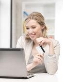 Mujer feliz con ordenador portátil y la tarjeta de crédito — Foto de Stock