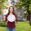 Young woman in casual clothes with wall clock — Photo