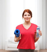 Smiling girl with bottle of water after exercising — Photo