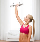Smiling woman with heavy steel dumbbell — Stock fotografie