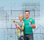 Smiling couple with paintbrush — Stock Photo