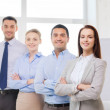 Smiling businesswoman in office with team on back — Stock Photo