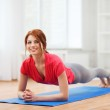 Smiling redhead teenage girl doing plank at home — Stock Photo #45461819