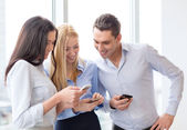 Smiling business team with smartphones in office — Stock Photo