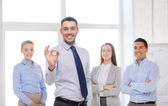 Smiling businessman showing ok-sign in office — Stock Photo