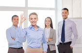Smiling businesswoman showing ok-sign in office — Stock Photo