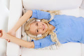 Smiling young girl in headphones at home — Stock fotografie