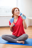 Smiling girl with bottle of water after exercising — Stok fotoğraf