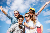 Smiling teenagers in sunglasses having fun outside — Stock Photo