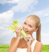 Woman biting piece of celery or green salad — Stock Photo