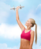 Smiling woman with heavy steel dumbbell — Stock Photo