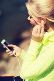 Mujer escuchando al aire libre de música — Foto de Stock