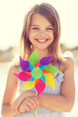 Happy girl with colorful pinwheel toy — Stockfoto